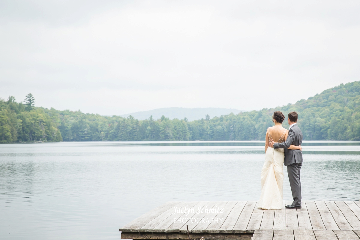 bride and groom gaze at lake on dock vt