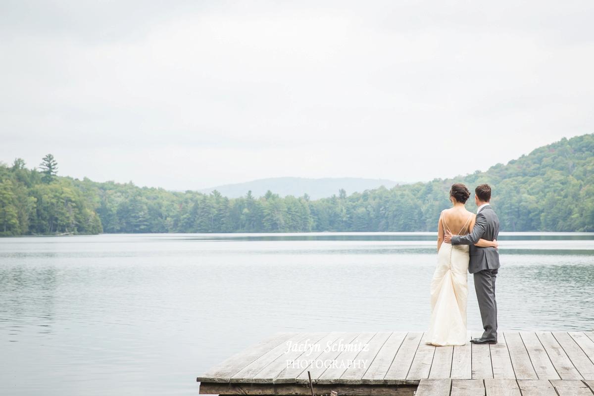 bride and groom gaze at lake on dock vt